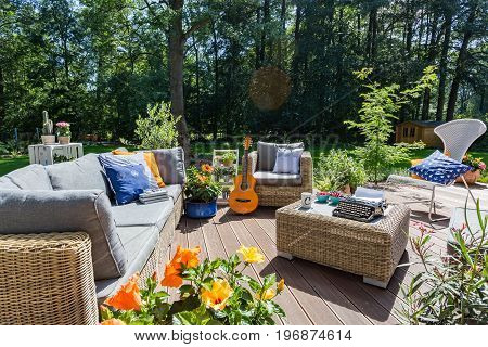 Spacious terrace with stylish wicker furniture in a sunny day of a summer