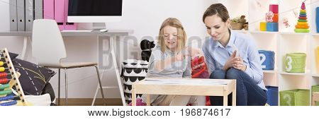School girl during her test on extra classes with psychotherapist