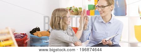 Young happy teacher congratulating good work to her little student