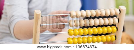 Close-up of young girl with studying problems counting on abacus