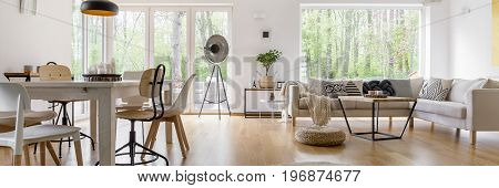Spacious cozy living room with big windows and glass door