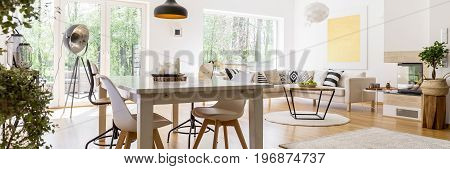 White spacious fully furnished living room with wooden table and corner sofa