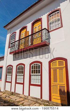 Facade view of old colored house with balcony and cobblestone in Paraty, an amazing and historic town totally preserved in the coast of the Rio de Janeiro State, southwestern Brazil