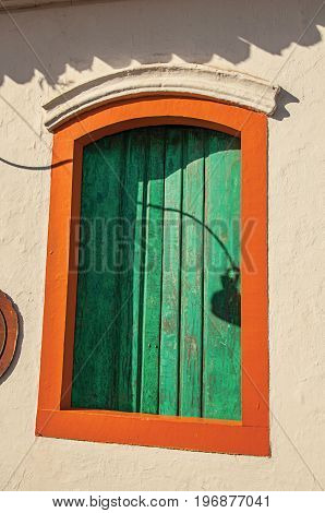 Close-up of colorful wooden window with closed green blinds in Paraty, an amazing and historic town totally preserved in the coast of the Rio de Janeiro State, southwestern Brazil