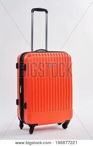 Personal luggage bag, white background. Modern red suitcase with handle. Case for tourism.