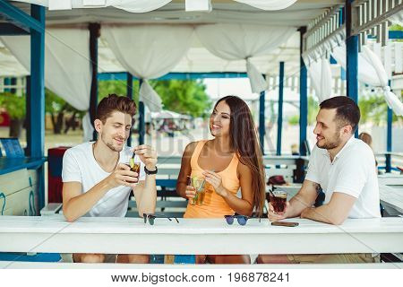 Lifestyle Friends toasting in summer vacation in a bar terrace on the beach. Two guys and a young woman are relaxing at the bar.