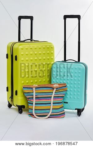 Two suitcases and bright handbag. Fashionable bags for holiday abroad.