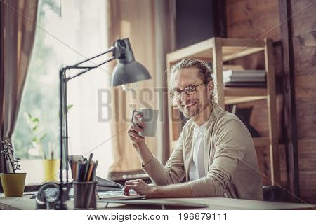 Man working on freelance at home, smiling holding mug. Male siiting at table, working at home.