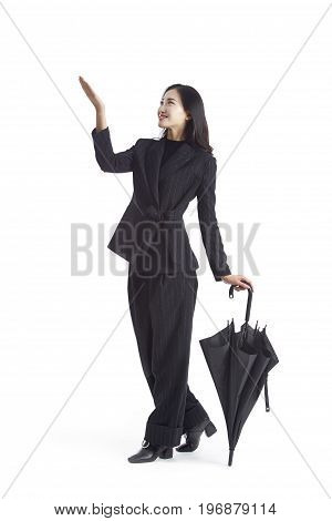 young asian businesswoman with folded black umbrella studio shot isolated on white background.