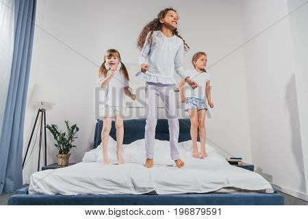 multiethnic little girls in pajamas jumping on bed at home