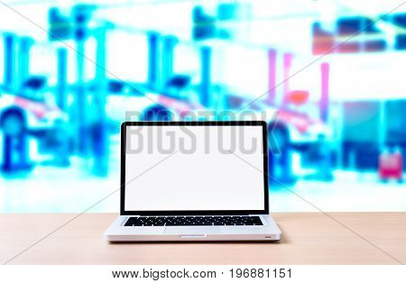 Laptop with blank screen on wood desk behind automotive business service centre background.