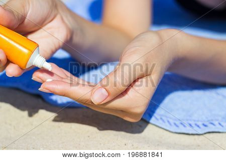 Woman's hand putting sunscreen on from a suncream bottle