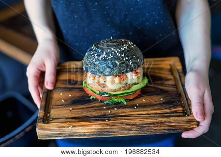 Close up woman holding delicious black burger with shrimps on wooden board in restaurant