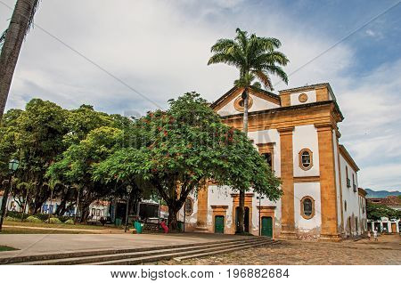 Overview of old colored church, garden with trees and cobblestone street in Paraty, an amazing and historic town totally preserved in the coast of the Rio de Janeiro State, southwestern Brazil