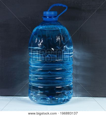 5 liters. Big plastic bottle of potable water barrel with handle on a dark background