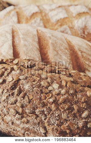 Bread texture crust closeup background, fresh baguette loaf and rye bread with sunflower seeds