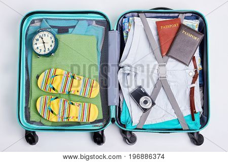 Opened blue wheeled suitcases. Packed with accessories bag for traveler.