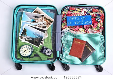 Ready suitcase for sea departure. Opened tourister luggage with beach accessories. Time to go to the sea.