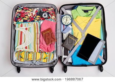 Essential things for going abroad. Suitcase with beach clothes and accessories.