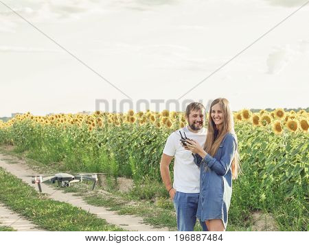Man and woman flying drone outdoors in countryside. Happy young couple standing together outdoors with woman holding a remote control for drone operation and man teaching.