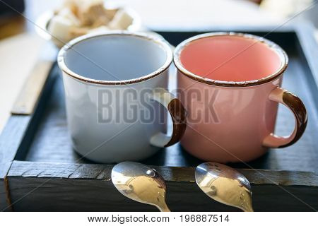 Close up vintage teaset with blue and pink metal mugs and spoons on wooden tray