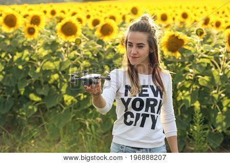 Portrait of a beautiful woman holding a mini drone on her hand. The girl stands against the background of a field of sunflowers. Drone is preparing to take off. Selective focus on drone.