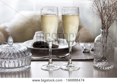 Pair of filled champagne flutes on the wedding table Mockup.
