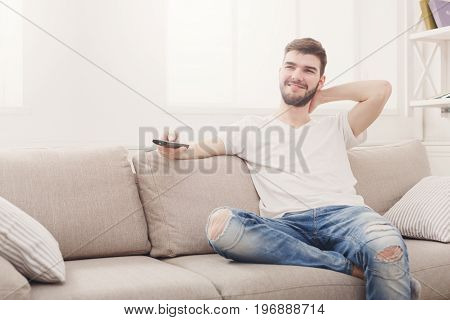 Young smiling man wathing tv at home. Happy guy pointing with remote control on tv-set, copy space
