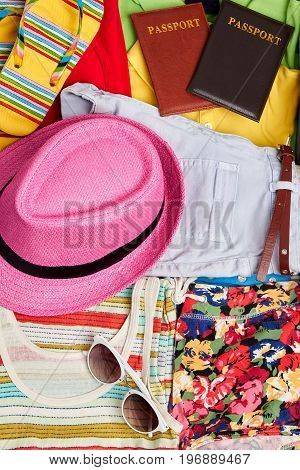 Personal woman things for vacation abroad. Hat, passports, glasses, clothes, sandals.