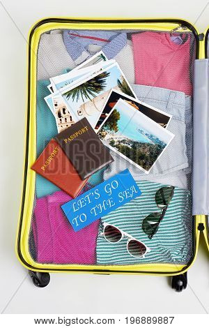 Opened yellow suitcase with accessories. Clothing stuff for summer journey.