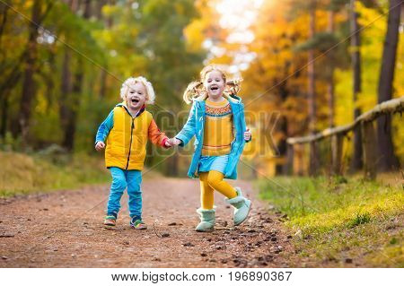 Kids play in autumn park. Children throwing yellow maple leaves. Boy and girl jump and run with oak leaf. Fall foliage. Family outdoor fun in autumn. Toddler kid and preschooler child in fall.