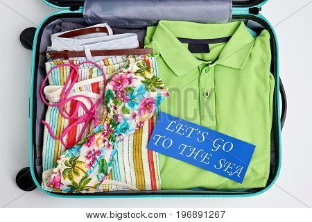 Clothing for sea in suitcase. Personal beach things in open tourister bag.
