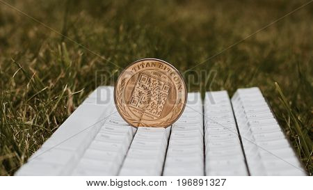 Cryptocurrency physical gold titan bitcoin with qr code on white keyboard in grass. poster