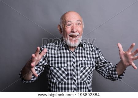 Excited senior man very glad to success, looking away and gesturing with hands, gray studio background