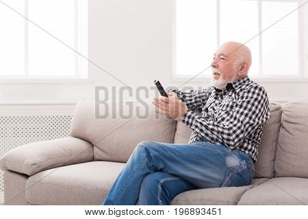 Emotional senior man watching tv, sitting on couch with remote controller, copy space