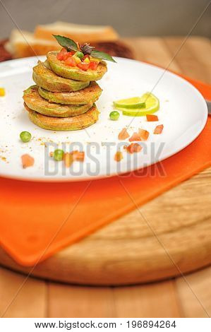 Vegetable fritters of zucchini on a wooden table