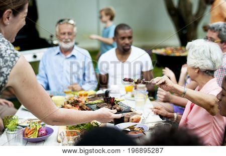 Diverse senior friends gathering having food together