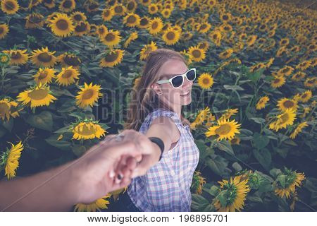 Young modern woman in sunglasses holding man's hand in sunflower field. Summertime and love concept.