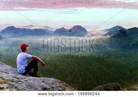 Film Grain. Adult Sportsman In White Shirt, Dark Trousars And Red Cap. Man Sit On Sharp Cliff