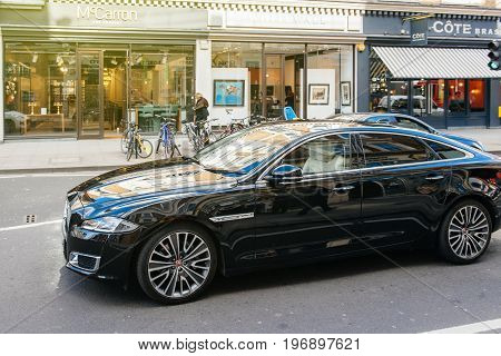 LONDON UNITED KINGDOM - MAR 9 2017: Luxury new black Jaguar XJ AUTOBIOGRAPHY LWB driving on the crowded london street with open shoppings and commerces in the background.