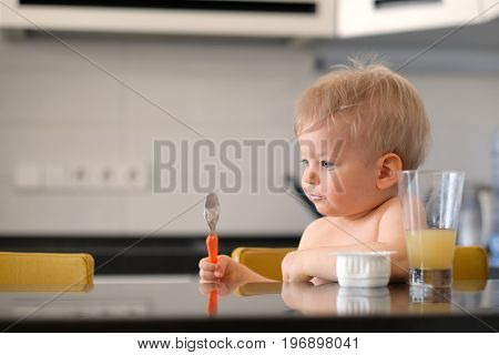 Adorable one year old baby boy eating yoghurt with spoon. Dirty messy face of toddler child.