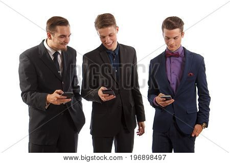 Three men in suits using their smartphones