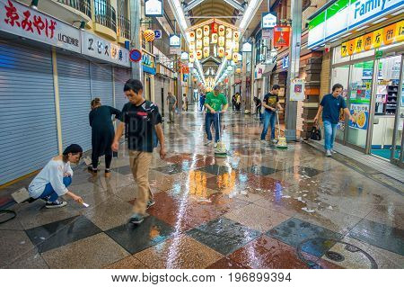 KYOTO, JAPAN - JULY 05, 2017: Unidentified people cleaning with brooms the exterior o their markets of shops and services, both traditional and modern.
