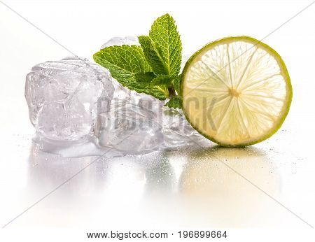 Ice cubes and slice of lime with mint leaf on white background