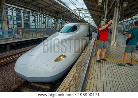 KYOTO, JAPAN - JULY 05, 2017: Unidentified man tajing a selfie with a train behind, JR700 shinkansen bullet train departing Kyoto station in Kyoto, Japan.