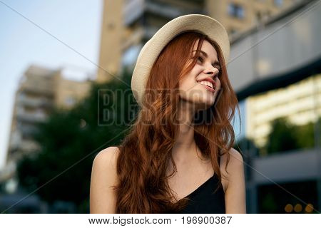 Young beautiful woman in a hat walking along a street in the city.