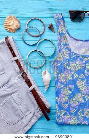Denim shorts and stylish shirt. Bracelets, seashells, sunglasses, sea background.