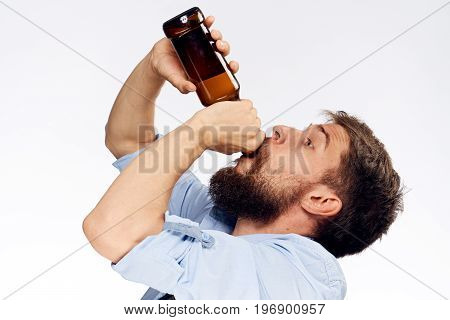 Man with a beard on a white isolated background drinking beer, alcohol, drunk.