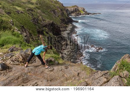 a woman practicing yoga along the scenic coast of Maui