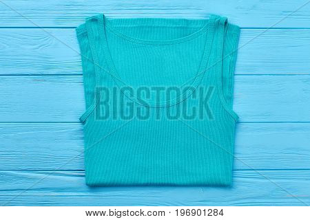 Turquoise t-shirt for sport activity. Single t-shirt isolated on blue wooden bakground.
